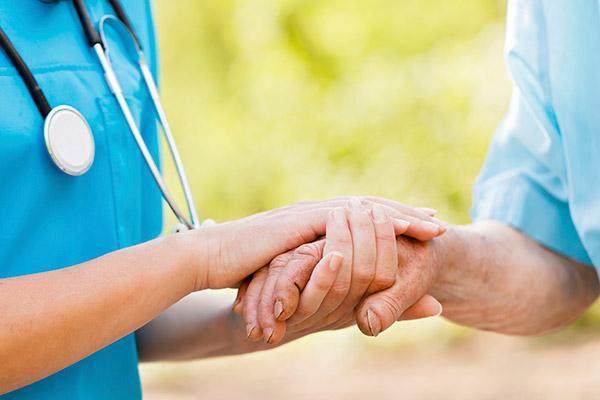 Doctor holding hand of senior.
