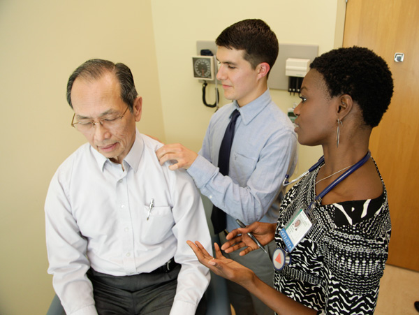 Clinician and student examine patient