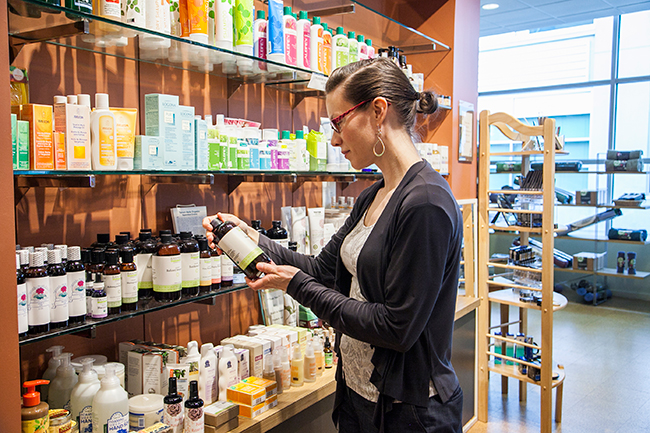 A customer looks at a product from a Dispensary shelf.