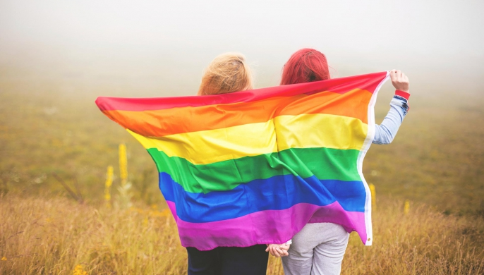 Two people holding a rainbow flag and holding hands.